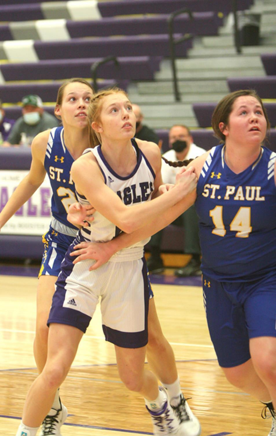Jenna Rauert (center) very frequently takes charge of the paint where it can get crowded quite often. The junior Lady Eagle and her mates play at home tomorrow, Friday, the 8th, and next Thursday, the 14th. (—photo by Lynn McBride)