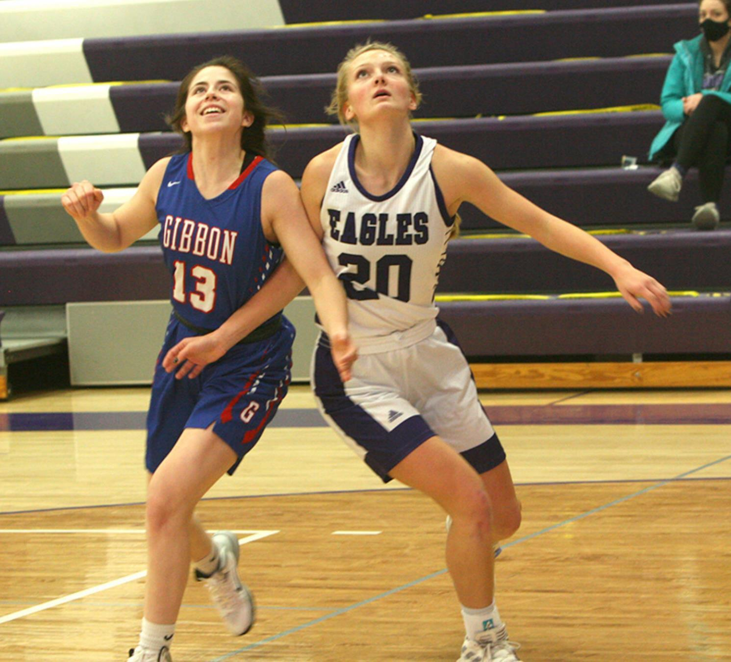 Gibbon's Desire Nunez (#13) and Wood River's Macie Peters jockey for position for a rebound in the renewal of the friendly Highway 30 rivalry on December 19. The Lady Eagles emerged from the contest with a decisive 62-36 victory. (–photo by Lynn McB