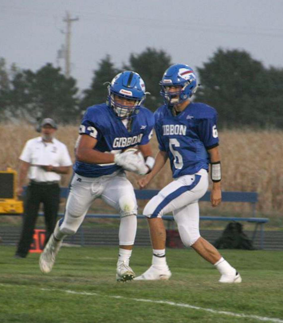 Jesus Hernandez (#23) takes a handoff from quarterback Matthew Weismann in Gibbon's 35-13 homecoming win over Centura. (–photo by Dennis Walker)