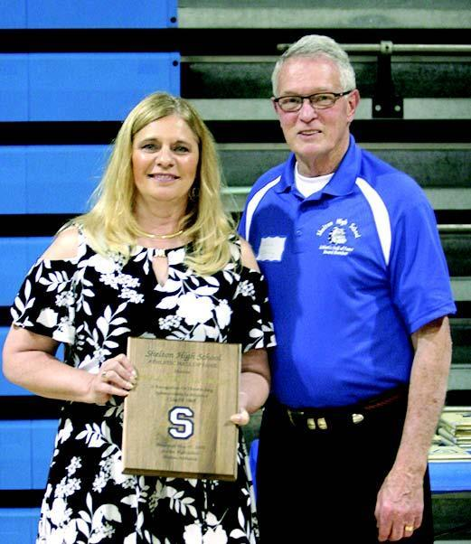 Track standout Paula West Mayfield is presented her plaque by Shelton Athletic Hall of Fame board member John Dority.