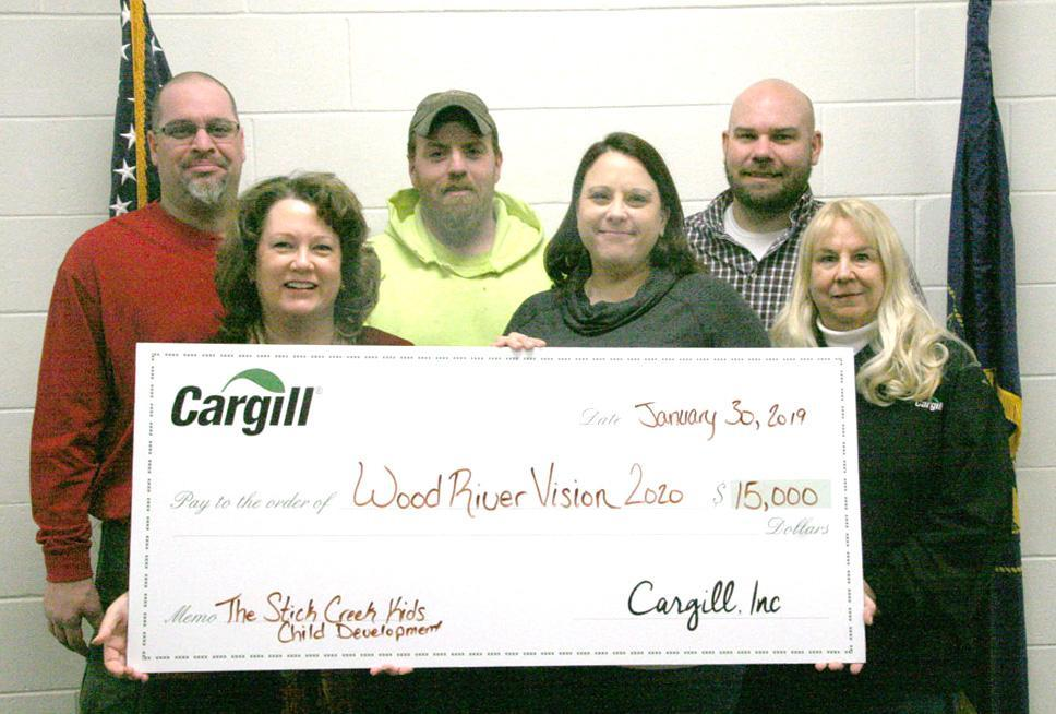 Representatives of Cargill presented Sara Arnett, representing Wood River Vision 20/20, with a check for $15,000 for the Stick Creek Kids Child Development project in Wood River on Wednesday, January 30. Pictured are, front row, left to right, Sara Arnett and Cargill representatives Tara Fortune and Patty Camp; and back row, Cargill representatives Jason Wiehn, Chad Shuda, and Levi Lammert. (–photo by Dennis Walker)