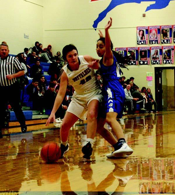 Samantha Walker tries to drive around Shelton defender Mayte Meza during the Tuesday night matchup of the Buffaloes and Bulldogs. Shelton won the contest 54- 35. (—photo by Dennis Walker)
