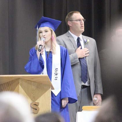 Shelton High graduate Lyndee Kautz performs the National Anthem as Secondary Principal Jeremy Weiseler looks on during commencement ceremonies for the Class of 2019 on Saturday. (–photo by Steve Glenn)