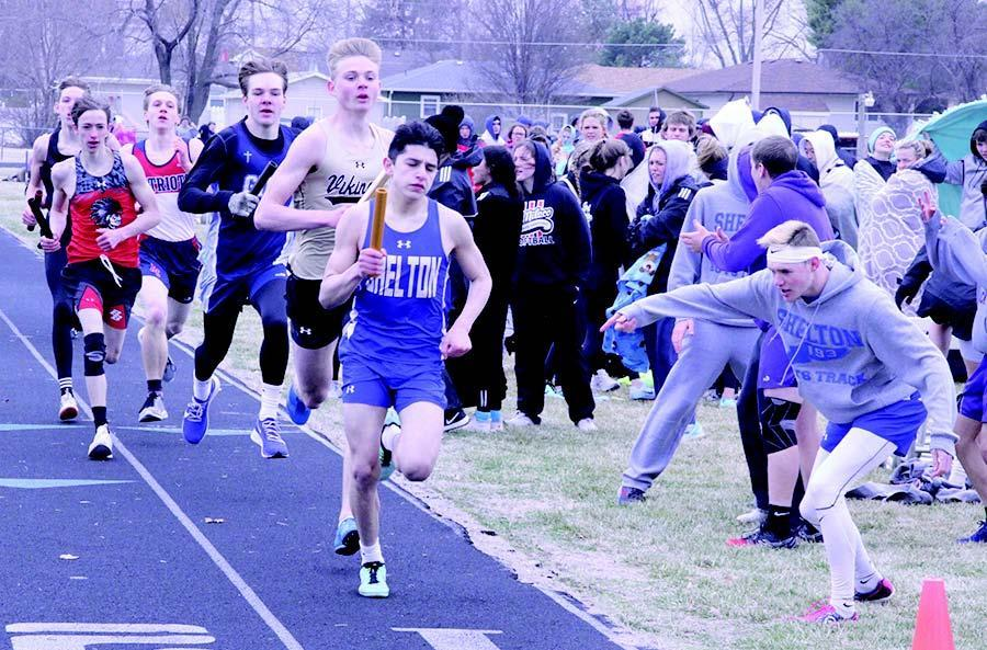 Shelton's Jesse Sauceda leads after the first lap of the 3200 meter relay event at GICC, with teammate Ry Cheney cheering him on. (—photo by Steve Glenn)